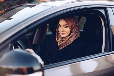 Young arabic woman in hijab driving a car Stockfoto