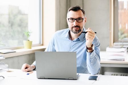40 jaar oude knappe man van middelbare leeftijd aan het werk op een laptopcomputer op kantoor. Man aan het werk op kantoor