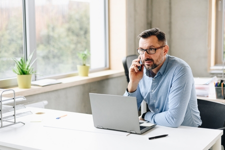Middle aged handsome businessman in shirt working on laptop computer in office. Man working in office Standard-Bild - 116596235