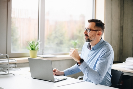 Middle aged handsome man in shirt working on laptop computer in office. Man working in office Standard-Bild - 116596236