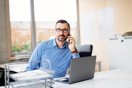 Middle aged handsome man in shirt working on laptop computer in office. Man working in office Standard-Bild - 116596237