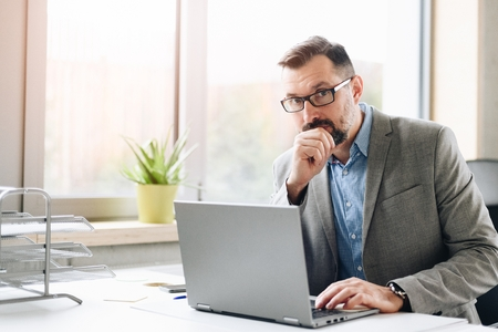Thoughtful middle aged handsome businessman in shirt working on laptop computer in office. Man working in office Standard-Bild - 116596239