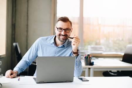 40 years old middle aged handsome man working on laptop computer in office. Man working in office