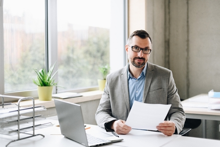 Happy middle aged handsome businessman in shirt working on laptop computer in office. Man working in office Standard-Bild - 116596242