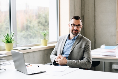 Happy middle aged handsome businessman in shirt working on laptop computer in office. Man working in office Standard-Bild - 116596241