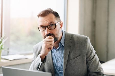 Durchdachter gutaussehender Geschäftsmann mittleren Alters im Hemd, der an Laptop-Computer im Büro arbeitet. Mann arbeitet im Büro