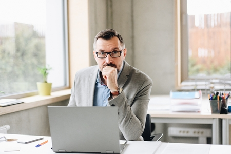 Middle aged handsome businessman working on laptop computer in office. Man working in office Standard-Bild - 116597429