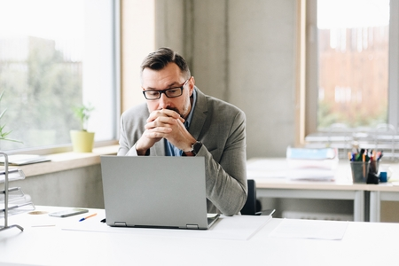Thoughtful middle aged handsome businessman in shirt working on laptop computer in office. Man working in office Standard-Bild - 116597428