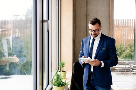 Middle aged handsome businessman in suit at office. Man working in office Standard-Bild - 116596288