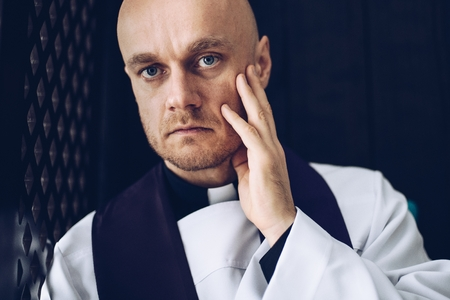 Catholic priest confessives in the confessional. Faith and religion Stock Photo