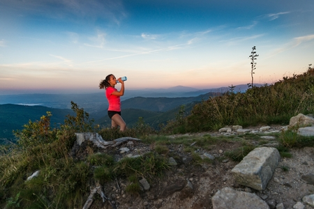 Woman cross country runner drinking water in mountains at summer. Woman running. Silesian Beskid, Szczyrk Standard-Bild - 116597521