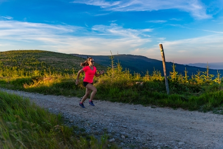 Young woman cross running in mountains at summer. Woman running. Silesian Beskid, Szczyrk, Poland Standard-Bild - 116597523