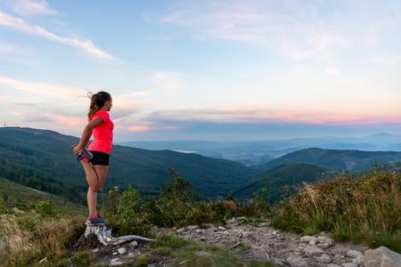 Woman cross country runner quads stretching in mountains at summer. Woman running. Silesian Beskid, Szczyrk Standard-Bild - 116597528