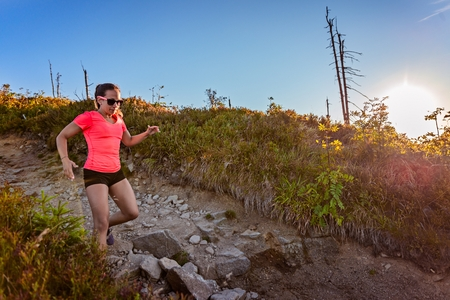 Young woman trail running in mountains at summer. Woman running Standard-Bild - 116596317