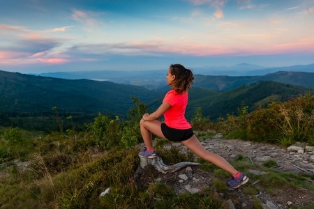 Woman cross country runner stretching in mountains at summer. Woman running. Silesian Beskid, Szczyrk Standard-Bild - 116596321