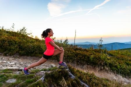 Woman cross country runner stretching in mountains at summer. Woman running. Silesian Beskid, Szczyrk Standard-Bild - 116596320