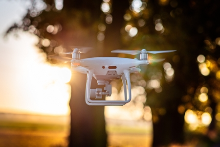 Professional drone with camera in flight. White drone quadrocopter. Unmanned aerial vehicle Standard-Bild - 116596319