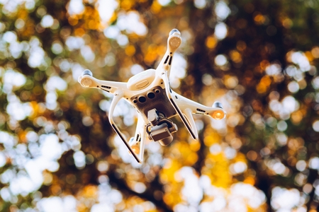 Unmanned aerial vehicle. White drone quadrocopter in flight Standard-Bild - 116596322