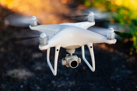 White drone quadrocopter in flight. Unmanned aerial vehicle Standard-Bild - 116596323