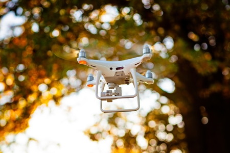 Professional drone with camera in flight. White drone quadrocopter. Unmanned aerial vehicle Standard-Bild - 116596330