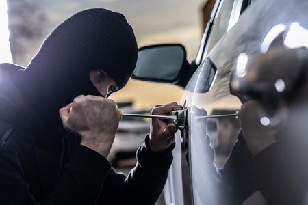 Car thief opening stolen car doors. Car thief, car theft Standard-Bild - 116597561