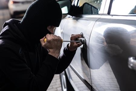Car thief opening stolen car doors. Car thief, car theft Standard-Bild - 116597559