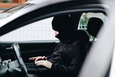 Masked thief hacker in a balaclava disarming car security systems and stealing a car Standard-Bild - 116597565