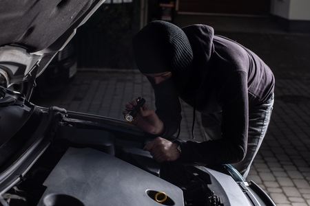 Masked thief in a balaclava with flashlight trying to steal a car Standard-Bild - 116597567