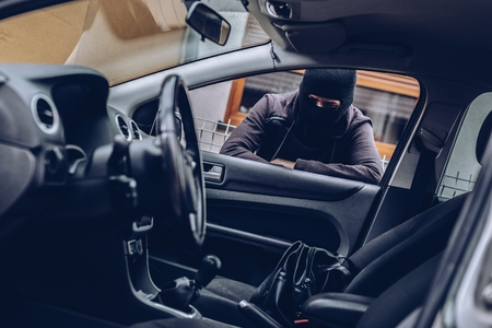 Thief in a balaclava stealing woman's bag from car