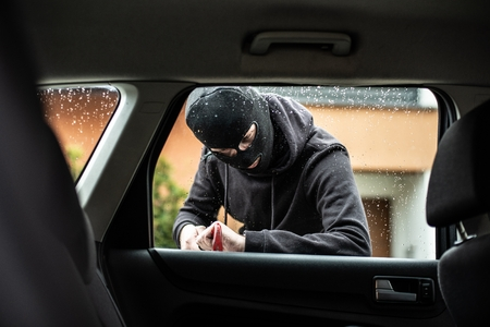 Car thief in a balaclava is trying to break into a car using a crowbar Standard-Bild - 116597569