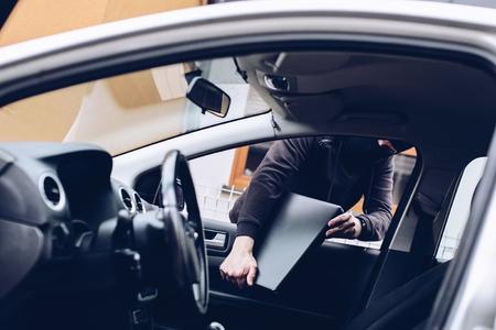 Masked thief in a balaclava stealing laptop computer from car Standard-Bild - 116597655
