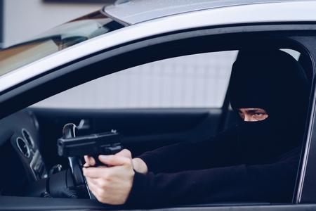 Masked terrorist with pistol gun in car Standard-Bild - 116596367