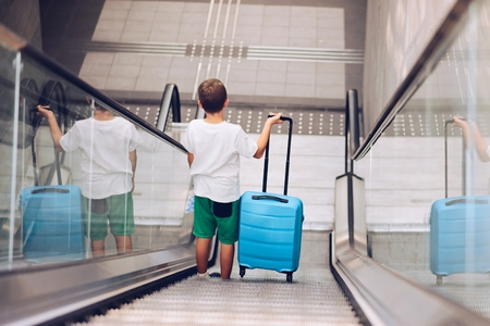Child with blue baggage suitcase on escalator. Child on travel