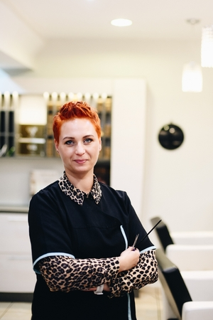 Woman hairdresser posing with scissors. Small business concept