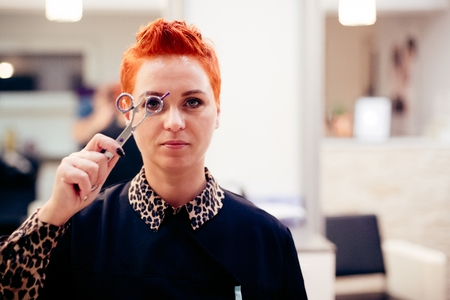 Female hairdresser posing with scissors. Small business concept