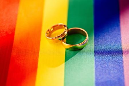 Dos anillos de bodas de oro en la bandera del arco iris. Matrimonio homosexual. Derechos y leyes LGBT Foto de archivo