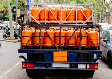 Gas delivery. Truck with orange propane gas tanks Imagens