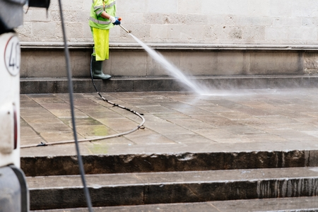 City cleaning worker cleaning street with water high pressure washer