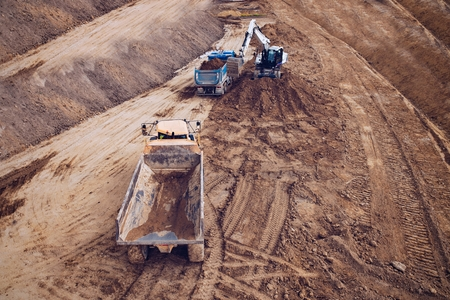 Aerial drone view on excavator loading sand on tipper truck. Road construction Imagens