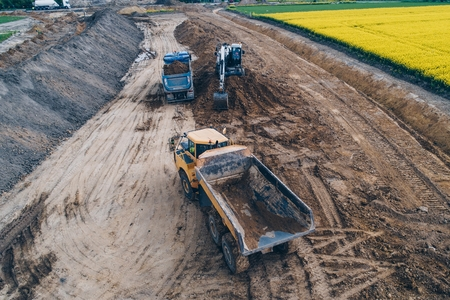 Aerial drone view on excavator loading sand on tipper truck. Road construction Banco de Imagens