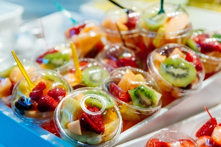 Plastic cups with delicious fruits for sale. Kiwi, pineapple and other juicy fruits in plastic cup. Takeaway fruits