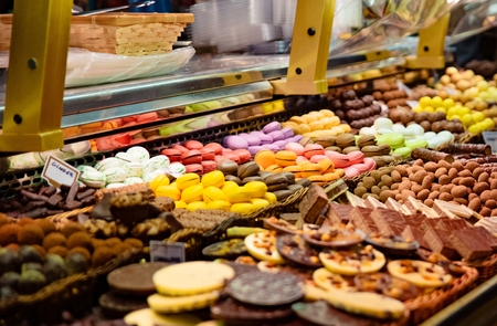 Colorful macaron cakes and other delicious cakes on display in candy store