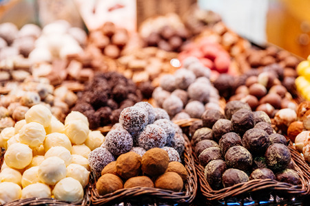 Sweet balls in white chocolate, coconut and dark chocolate on display in confectionary candy store