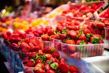 Plastic baskets with fresh red strawberries for sale on market stall Banco de Imagens