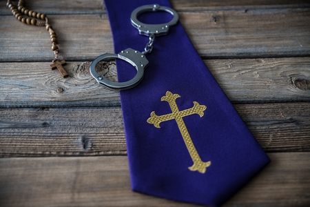 Handcuffs and catholic church symbols. Church and crime