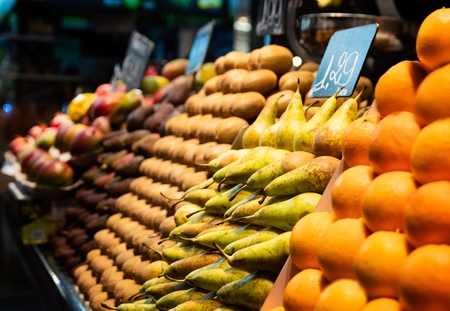 Pears and kiwi fruits and oranges on market stall display Banco de Imagens