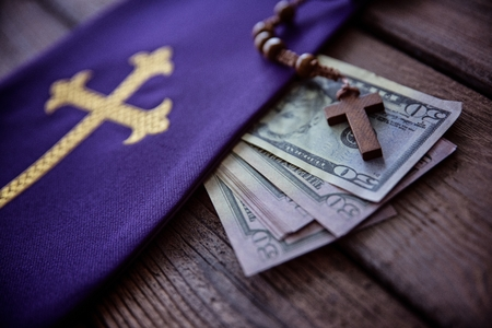 Wooden rosary and catholic church symbols and money. Church and money