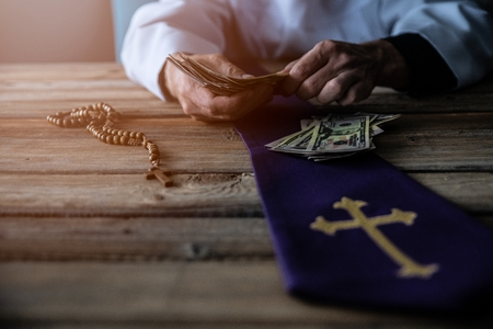 Priest counting money in his hand. Church and money