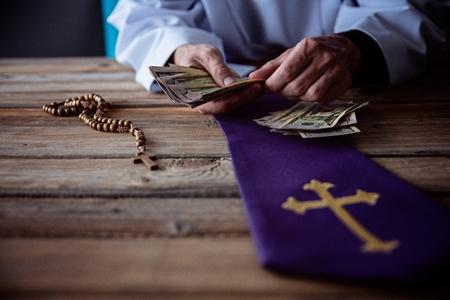 Ksiądz liczy pieniądze w ręku. Kościół i pieniądze Zdjęcie Seryjne