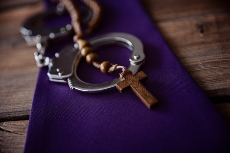 Catholic church symbols and handcuffs. Church and crime Stock Photo - 123507420